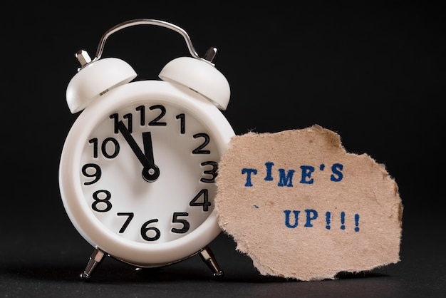 Times up text on torn brown paper near the white alarm clock against black background