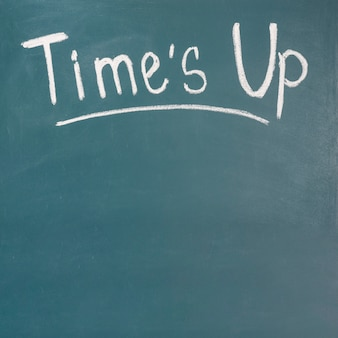 Times up written on green blackboard with chalk
