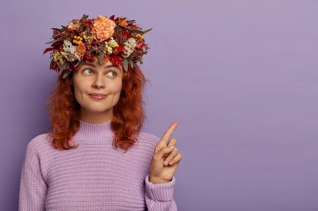 생강 머리를 가진 소심하고 사랑스러운 아가씨는 신중하게 바라보고 멋진 광고를 보여주고 보라색 배경에 고립 된 수제 화환을 착용합니다.