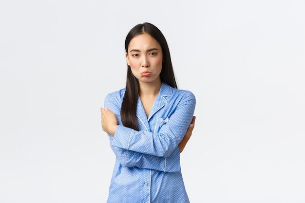 Робкая и расстроенная милая азиатская девушка в синей пижаме чувствует себя неуверенно и расстроенной