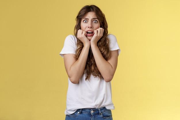 臆病な不安強烈なあえぎ若い怖い魅力的な女性ため息をつくショックを受けたおびえたホールド手顔を噛む爪恐怖表現恐怖立っている黄色の背景を見つめるカメラを振った。