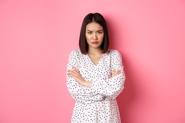 Timid and offended asian girl cross arms on chest, staring defensive and insulted at camera, standing in dress over pink background.