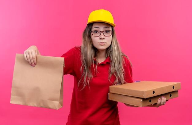 Timida giovane ragazza delle consegne in polo rossa e cappuccio giallo che tiene scatole per pizza e pacchetto di carta che guarda l'obbiettivo