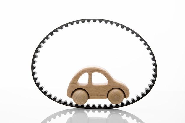 白い背景の上のおもちゃの車とタイミングベルト