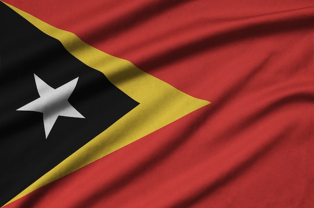 Timor leste flag  is depicted on a sports cloth fabric with many folds.