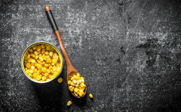 缶詰のトウモロコシと缶とスプーン。暗い素朴な背景に