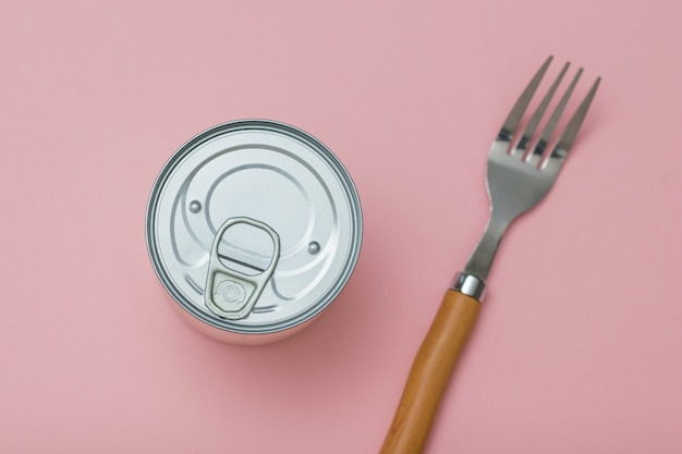 A tin can and a fork on a pink background. universal container for canning.