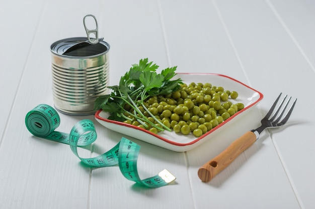 Консервная банка, зеленый горошек, вилка и измерительная лента на деревянном столе. диетическое вегетарианское питание.