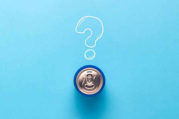 Консервную банку с напитком на синем фоне с вопросительным знаком. минимализм. понятие неизвестного напитка, попробуйте первый раз flat lay, вид сверху.