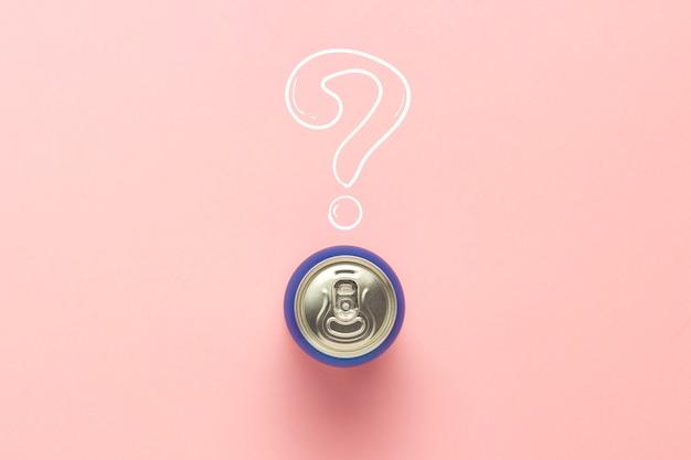 Консервную банку с напитком на розовом фоне с вопросительным знаком. минимализм. понятие неизвестного напитка, попробуйте первый раз flat lay, вид сверху.
