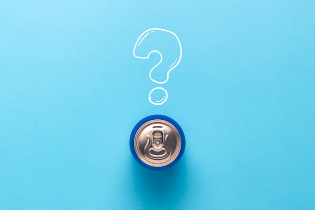 Tin can with a drink on a blue background with a question mark. minimalism. concept of an unknown drink, try the first time flat lay, top view.