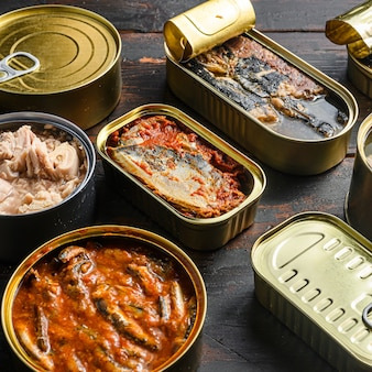 Tin cans for fish with different types of seafood, opened and closed cans with saury, mackerel, sprats, sardines, pilchard, squid, tuna, over dark wood old table close up side ciew.