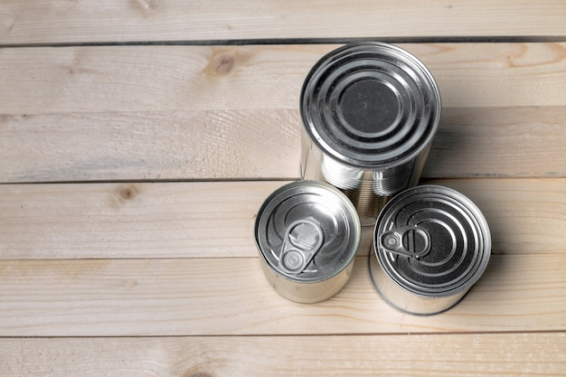 Tin cans for food on wooden