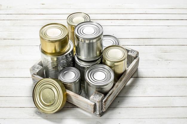 Жестяные банки с едой в ящике.