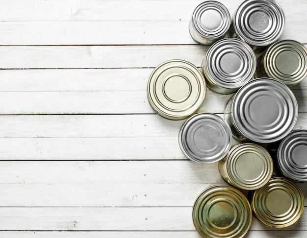 白い木製のテーブルの上の食品とブリキ缶