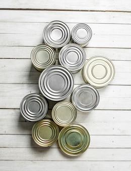 食品と缶。白い木製のテーブルの上。