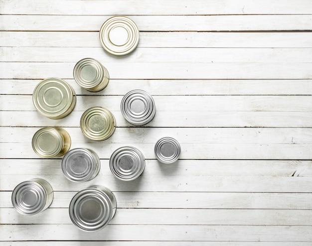 白い木製のテーブルの上の食品とブリキ缶。