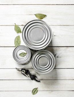 Tin cans with food and opener. on a white wooden table.