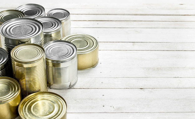 Tin cans with food on white wooden table