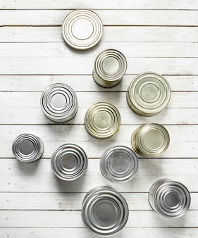 Tin cans with food on white wooden table.
