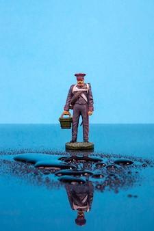水たまりの前にバケツを持ったナポレオン戦争の形をしたブリキの兵士が立っている