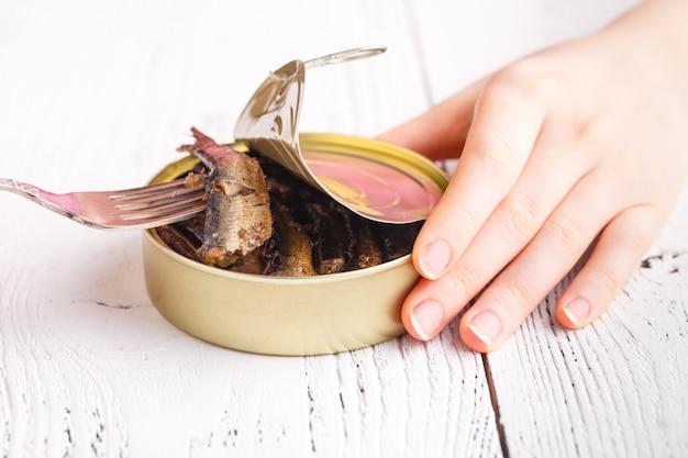 Маленькая копченая рыба в tincan на столе с вилкой