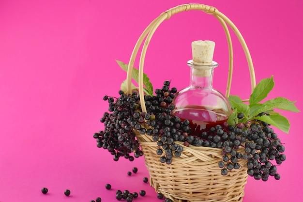 Tincture of elderberry berries in a bottle in a basket