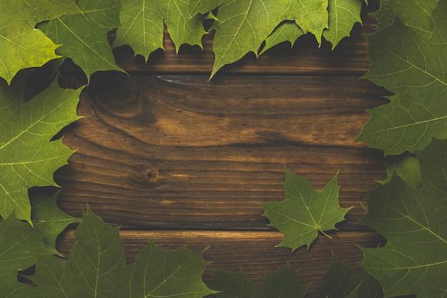 木製の背景にカエデの葉のフレームの着色画像。テキスト用のスペース。フラットレイ。