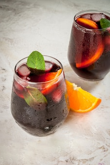 Традиционный испанский летний освежающий напиток, коктейль, tinto de verano. с вином, льдом и кусочками свежего апельсина. на белом каменном столе, скопируйте пространство