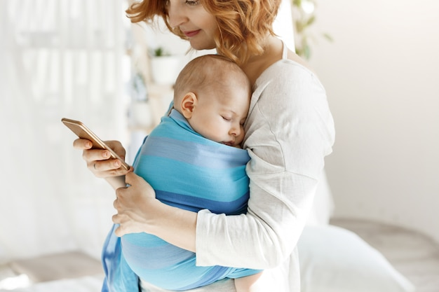 Tiny baby boy having pleasant dreams in baby sling while mother rests and looking through social networks on smartphone. family, lifestyle concept.