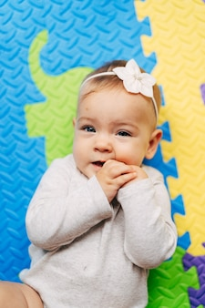 Tiny baby girl with a flower on her head in a white blouse lies on a multicolored rug