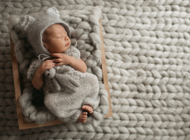 Tiny baby in grey clothes sleeps on woolen blanket