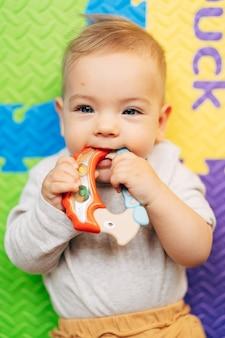 흰색 바디 수트를 입은 작은 아기가 컬러 러그에 누워 밝은 딸랑이를 잡고 갉아 먹습니다.