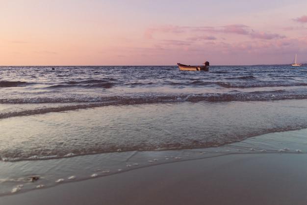외로운의 화려한 일몰 개념에 바다에 고립 된 작은 보트