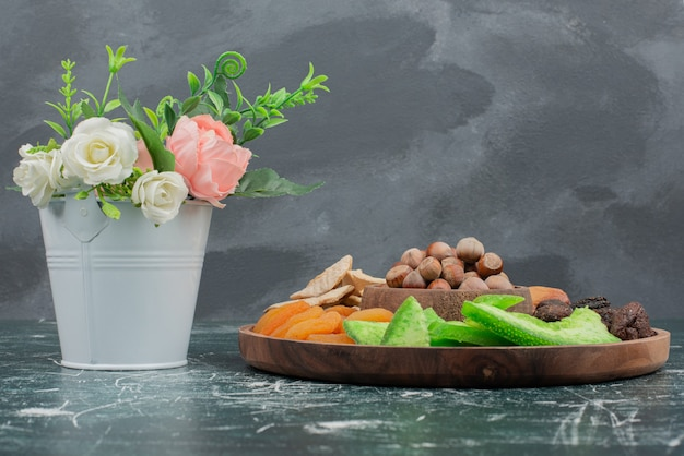 Tiny bouquet with wooden plate of dried fruits on marble wall .