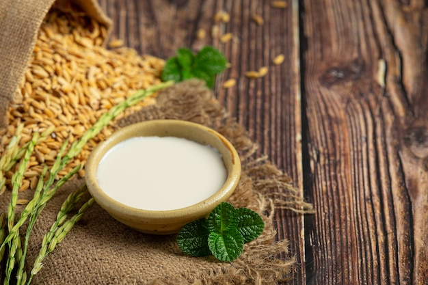 나무 바닥에 얹은 쌀 plnt와 쌀 씨앗을 가진 작은 쌀 우유 그릇