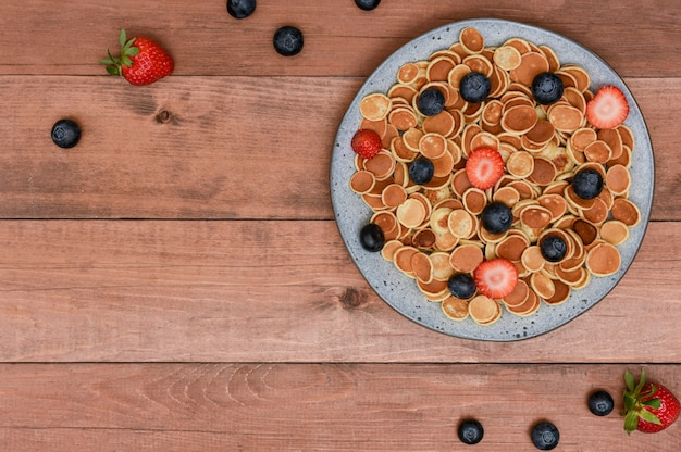Tiny cereal mini pancakes in a grey bowl with strawberries and blueberries on wood background.