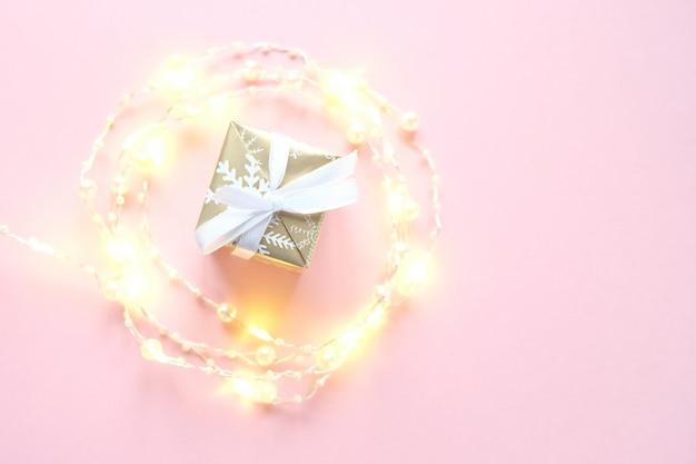 Tiny elegant christmas lights border. round shape made with garland on pink background.