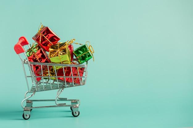 Piccole confezioni regalo messe nel mini carrello sul pavimento verde chiaro