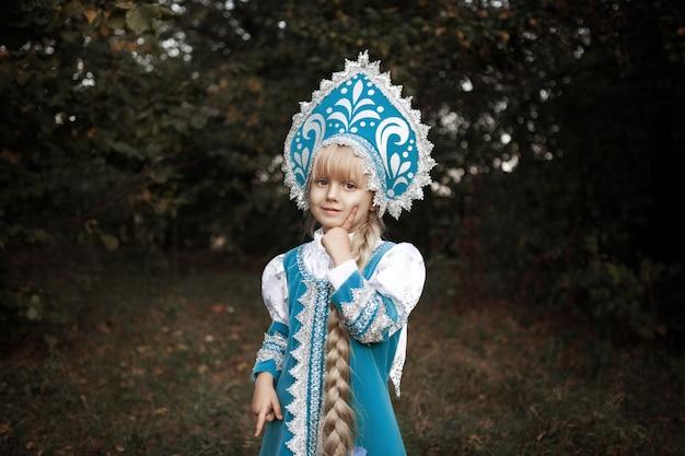 Маленькая девочка в сказочном русском костюме позирует на пленэре