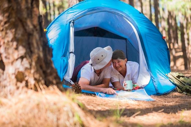행복하고 쾌활한 남녀 노인 은퇴 한 사람들을위한 나무에 작은 집. 대체 생활의 다음 단계를위한지도를보고 미소를 지으며 영원히 함께 여행합니다.