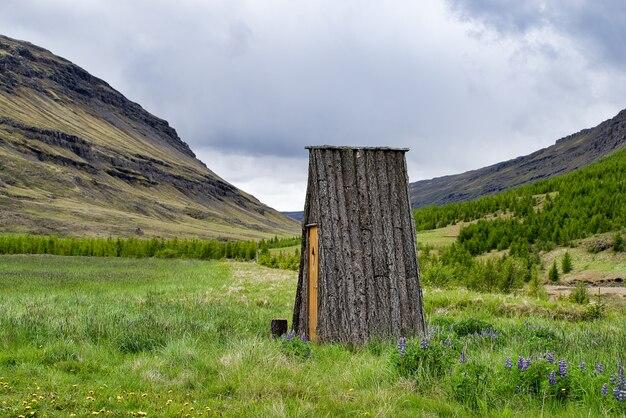 山の隣の牧草地にある、窓のない小さなアイスランドの丸太小屋。壁なし。屋根のみ。