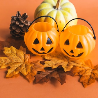 Tiny jack-o-lantern baskets near autumn symbols