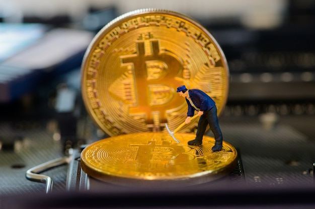 Tiny miner on golden bitcoin on electronic board