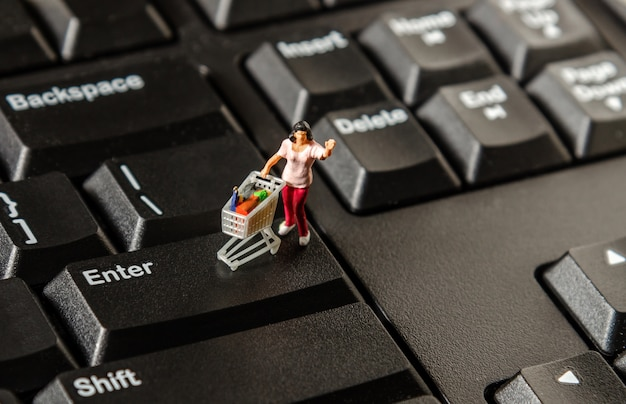 Tiny miniature figurine woman with shopping cart