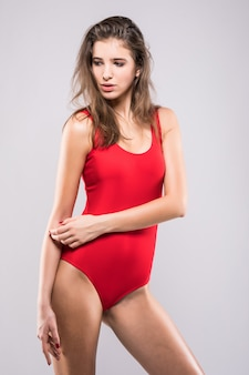 Tiny model girl in red swimming suite isolated on white background
