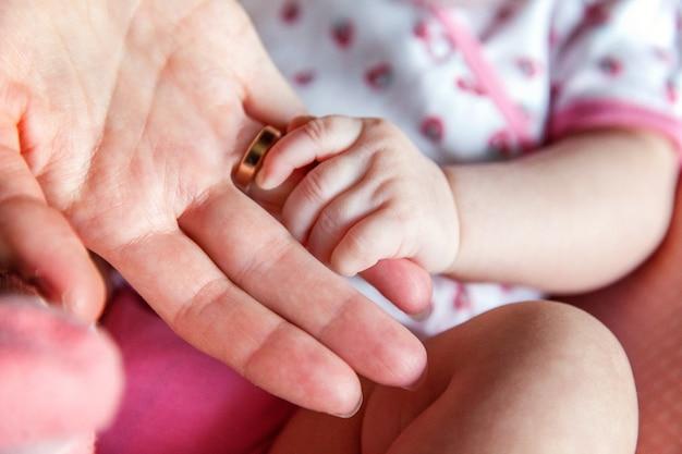 女性の形をした手のクローズアップに小さな新生児の手
