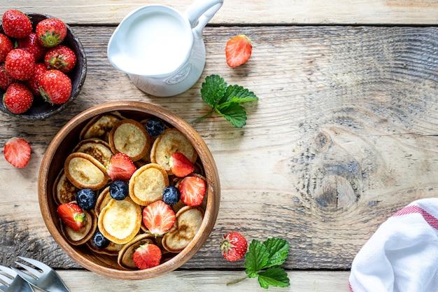 Крошечные блины из хлопьев и шоколадные мини-блины в деревянной миске с медом и клубникой