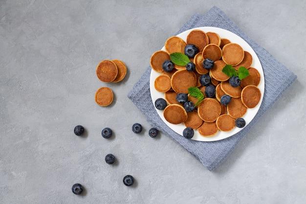 小さなパンケーキシリアルまたはお粥、ブルーベリーとミントと石の背景のトップビュー。健康全粒粉パンケーキ朝食コンセプト