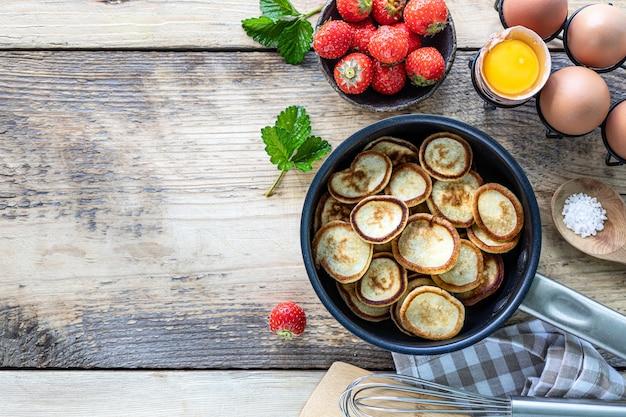Крошечные блины с клубникой в сковороде на деревянном фоне